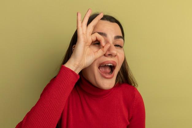 Vrolijke mooie blanke vrouw gebaren ok handteken en kijkt naar de camera door de vingers op olijfgroen