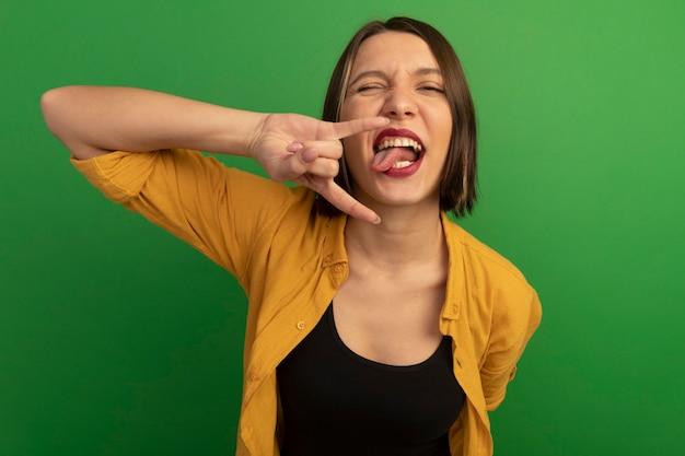 Vrolijke mooie blanke vrouw stak tong en gebaren hoorns handteken op groen