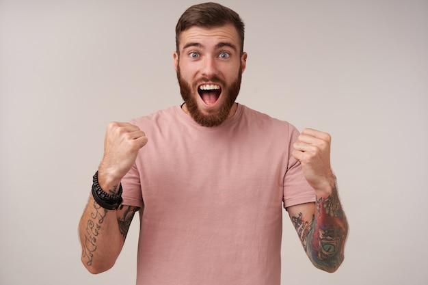 Vrolijke mooie blauwogige bebaarde man met tattooes die zich verheugt over het doelpunt gescoord met wijd open mond en ronde ogen, geïsoleerd op wit