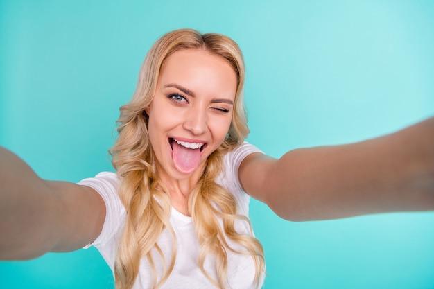 Vrolijke mooie blonde blogger dame maakt selfie show tong