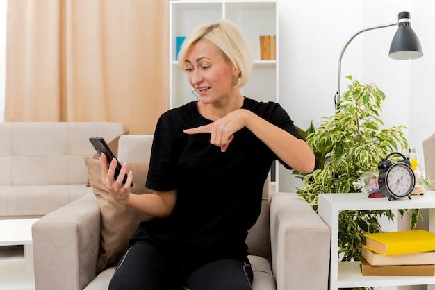 Vrolijke mooie blonde russische vrouw zit op fauteuil kijken en wijzend op telefoon in de woonkamer