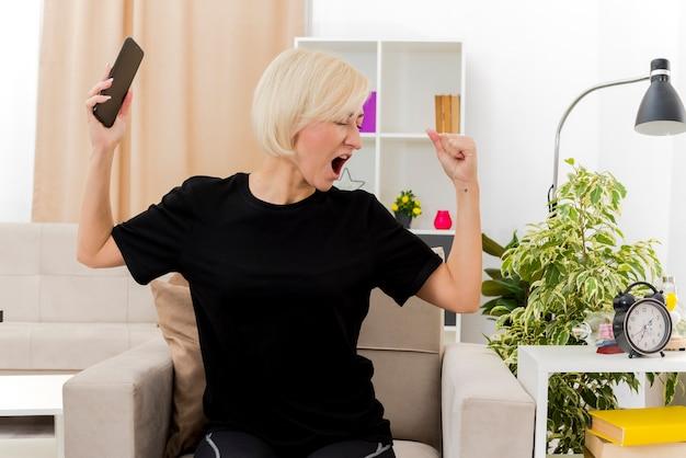 Vrolijke mooie blonde russische vrouw zit op fauteuil vuist houden en telefoon kijken kant in de woonkamer te houden