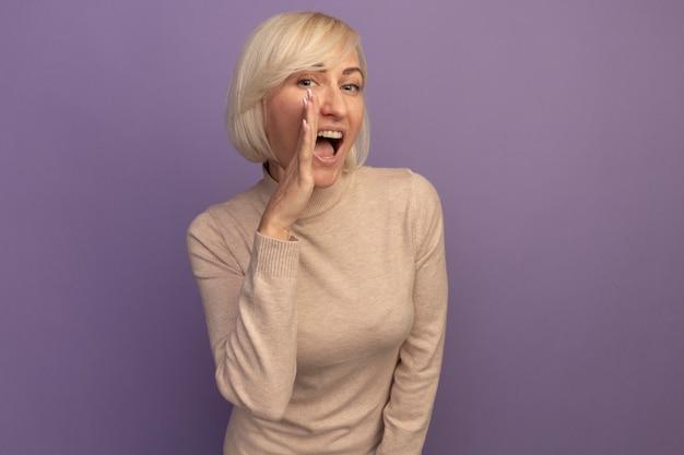 Vrolijke mooie blonde slavische vrouw houdt de hand dicht bij de mond op paars