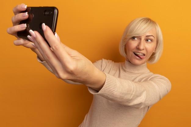 Vrolijke mooie blonde slavische vrouw steekt tong uit en kijkt naar telefoon die selfie geïsoleerd op oranje muur neemt