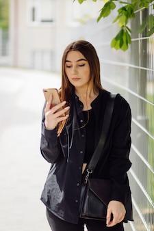 Vrolijke mooie brunette vrouw in goed humeur telefoon buiten gebruiken