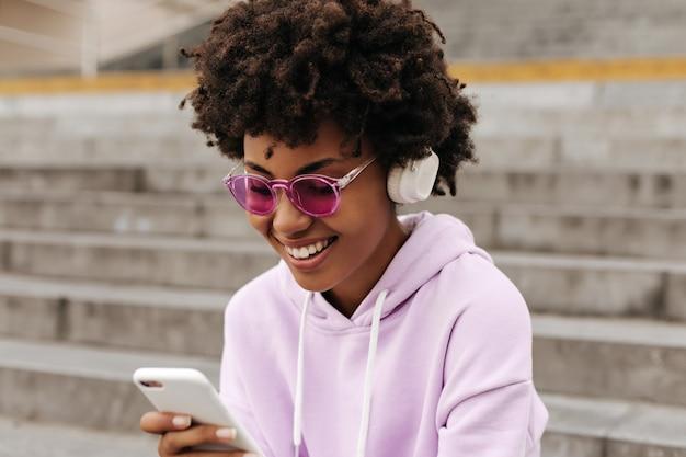 Vrolijke mooie brunette vrouw in paarse hoodie, roze zonnebril luistert naar muziek in koptelefoon, houdt telefoon vast en glimlacht naar buiten