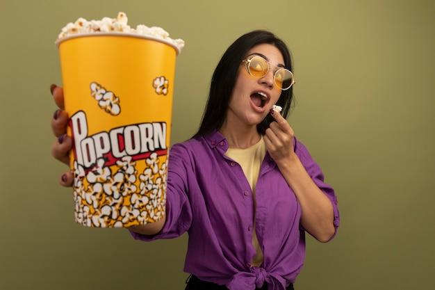 Vrolijke mooie brunette vrouw in zonnebril houdt en eet emmer popcorn opzoeken geïsoleerd op olijfgroene muur