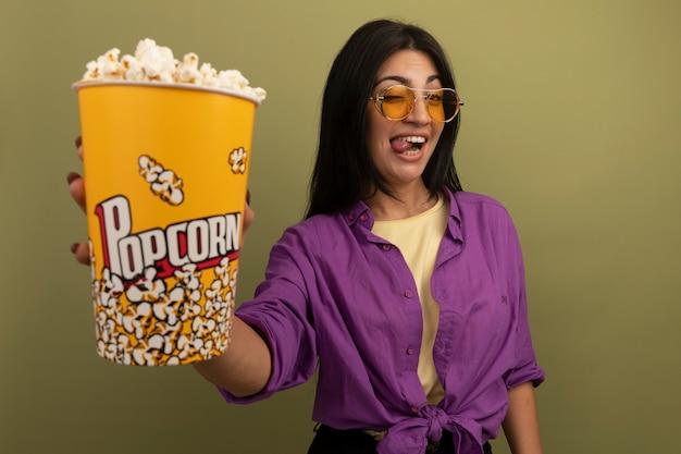 Vrolijke mooie brunette vrouw in zonnebril steekt tong uit en houdt emmer popcorn geïsoleerd op olijfgroene muur