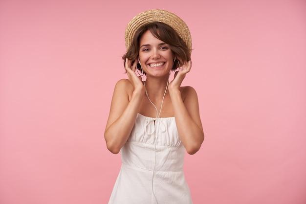 Vrolijke mooie brunette vrouw met kort kapsel dragen witte zomerjurk en strooien hoed, luisteren naar muziek met koptelefoon en kijken met een brede glimlach, geïsoleerd