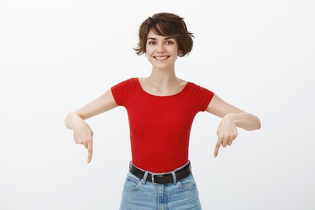 Vrolijke mooie brunette vrouw wijzende vingers naar beneden bij aankondiging