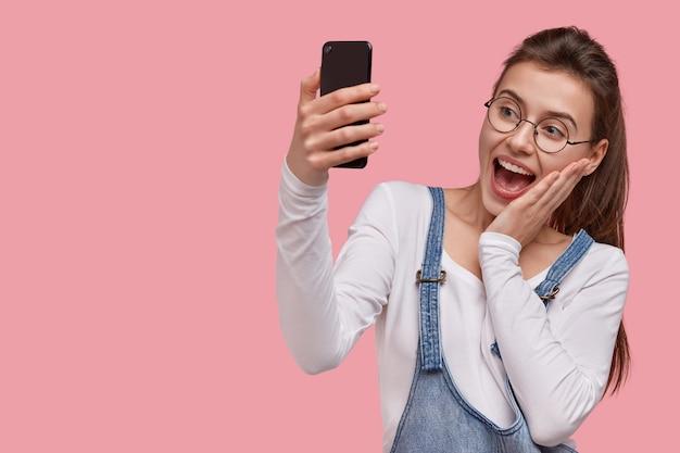 Vrolijke mooie dame heeft een donkere paardenstaart, raakt de wangen met de handpalm, opent de mond van verbazing, houdt een moderne mobiele telefoon vast