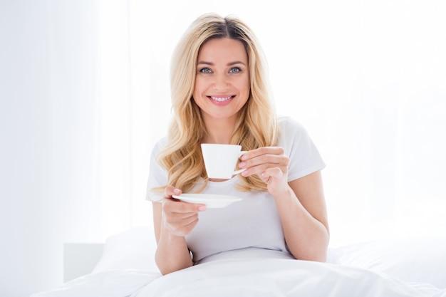 Vrolijke mooie dame liggend gezellig bed drink verse warme koffie draag pyjama