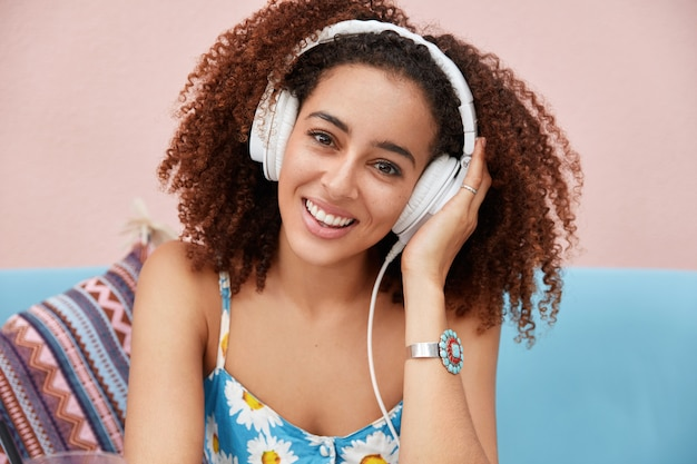 Vrolijke mooie donkere vrouw draagt een grote moderne koptelefoon, luistert naar aangename muziek terwijl ze thuis rust tijdens vrije dag op de universiteit of op het werk.
