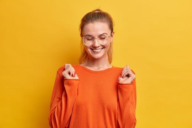 Vrolijke mooie duizendjarige vrouw glimlacht breed, sluit de ogen, heft gebalde vuisten op, draagt een casual oranje trui, een optische bril,