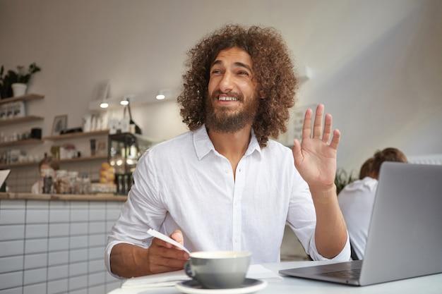 Vrolijke mooie gekrulde man met baard ontmoeten bekende persoon en zijn hand zwaaien, op afstand werken met laptop, poseren tijdens luncheonette interieur