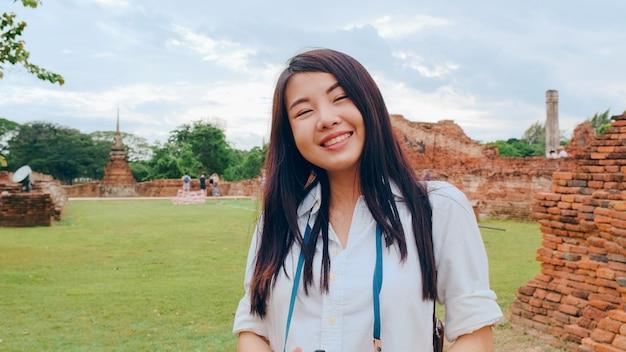 Vrolijke, mooie jonge aziatische backpacker-bloggervrouw met camera maakt foto's, reizend rond de pagode in de oude stad