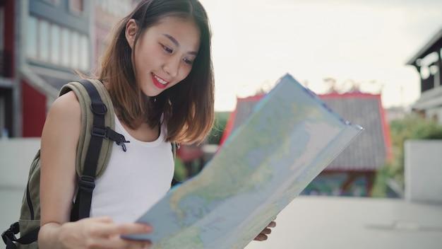 Vrolijke mooie jonge aziatische backpacker vrouw richting en kijken op de kaart van de locatie