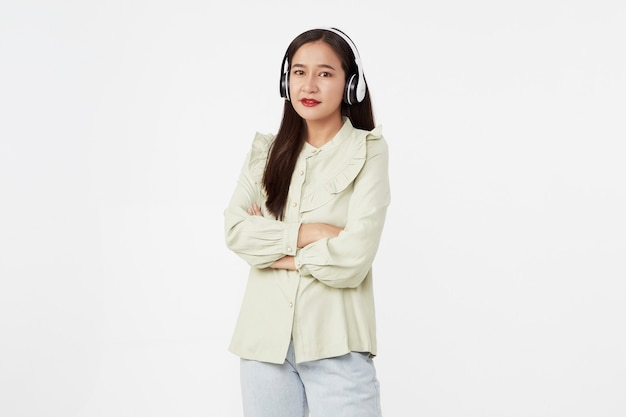 Vrolijke mooie jonge aziatische vrouw dansen genieten van muziek in draadloze koptelefoon op wit oppervlak