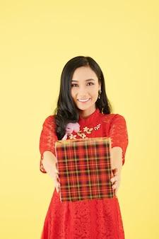 Vrolijke mooie jonge aziatische vrouw die haar handen uitstrekt met een groot cadeau voor de viering van chinees nieuwjaar