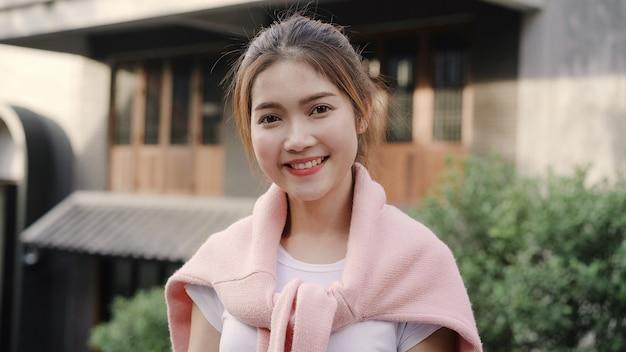 Vrolijke mooie jonge aziatische vrouw die het gelukkige glimlachen aan camera voelen terwijl het reizen in chinatown in peking, china.