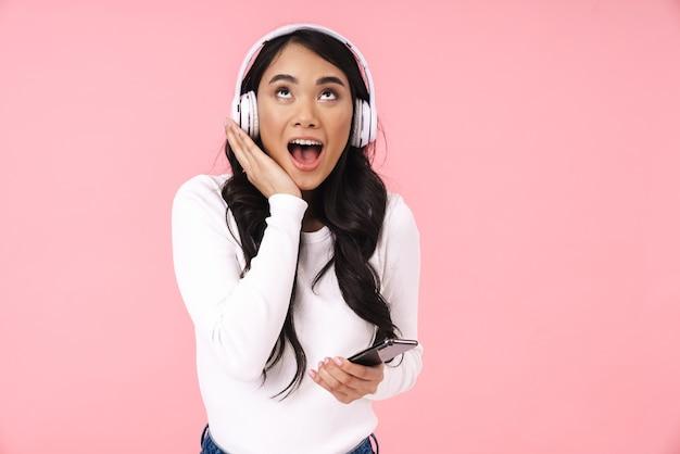 Vrolijke mooie jonge aziatische vrouw die naar muziek luistert met een draadloze koptelefoon geïsoleerd, met mobiele telefoon