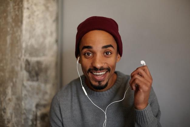 Vrolijke mooie jonge bebaarde man met donkere huid kijkt met charmante glimlach, houdt oortje vast en wordt verrast, draagt een grijze trui en bordeauxrode hoofdtooi