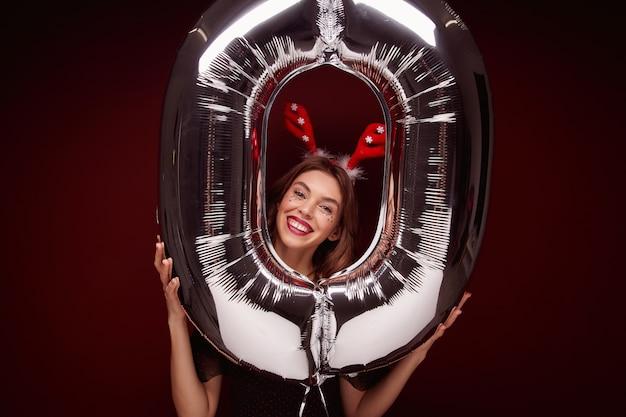 Vrolijke mooie jonge brunette vrouwelijke dame met avond make-up poseren met nummer luchtballon, nieuwjaarsfeest voorbereiden