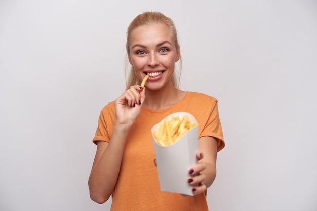 Vrolijke mooie jonge dame met lang blond haar gelukkig kijken naar de camera en smling wijd tijdens het eten van frietjes, gekleed in vrijetijdskleding terwijl staande op witte achtergrond