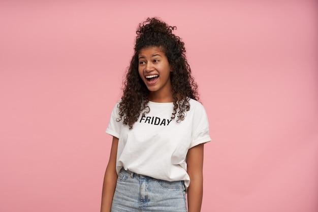 Vrolijke mooie jonge donkerhuidige brunette vrouw met lang krullend haar casual kapsel dragen terwijl poseren op roze, vrolijk opzij kijken en lachen met brede mond geopend