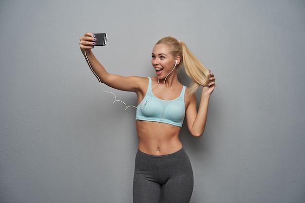 Vrolijke mooie jonge gezonde blonde vrouwelijke dame met paardenstaart kapsel mobiele telefoon in opgeheven hand houden en breed glimlachen naar de camera tijdens het maken van selfie, geïsoleerd over grijze achtergrond