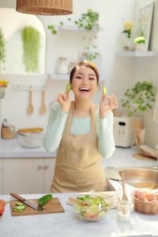 Vrolijke mooie jonge huisvrouw die plezier heeft tijdens het koken in de keuken