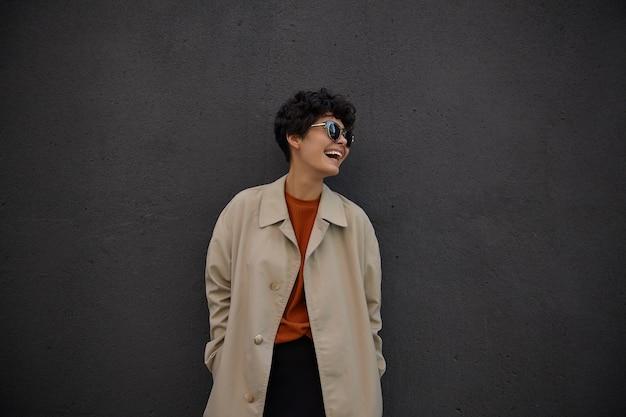 Vrolijke mooie jonge krullende vrouw met casual kapsel gelukkig opzij kijken en vreugdevol lachen, handen in zakken van haar stijlvolle beige loopgraaf houden