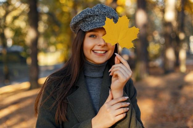 Vrolijke mooie jonge lachende vrouw met een hoed in een modieuze jas bedekt haar gezicht met een gele herfstblad in het park. geniet van het herfstweer.
