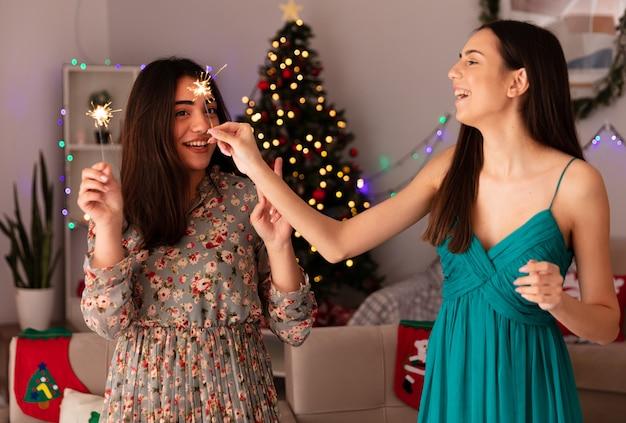 Vrolijke mooie jonge meisjes houden sterretjes thuis genieten van kersttijd Gratis Foto