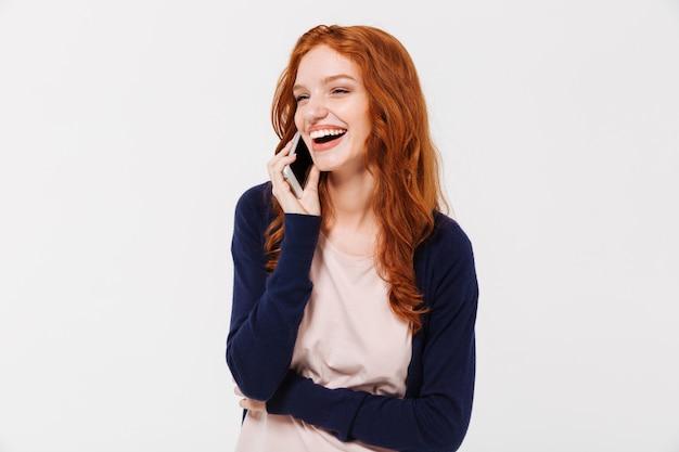 Vrolijke mooie jonge roodharige dame praten via de mobiele telefoon.