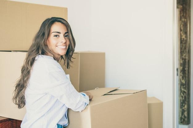 Vrolijke mooie jonge spaanse vrouw spullen uitpakken in haar nieuwe appartement, staande in de buurt van stapels kartonnen dozen