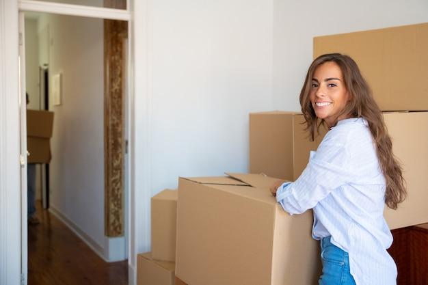 Vrolijke mooie jonge spaanse vrouw spullen uitpakken in haar nieuwe appartement, staande in de buurt van stapels kartonnen dozen,