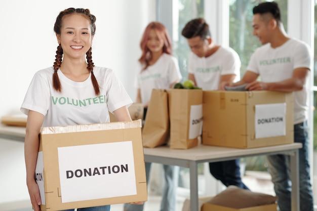 Vrolijke mooie jonge vietnamese vrouw met grote doos boodschappen ingepakt voor liefdadigheidscentrum of kerk