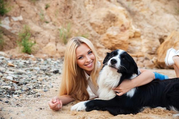 Vrolijke mooie jonge vrouw die haar hond rust en knuffelt op het strand