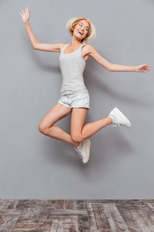 Vrolijke mooie jonge vrouw die in de lucht over grijze muur springt