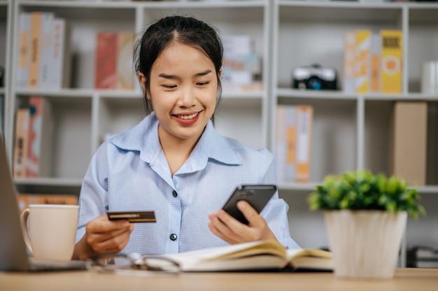 Vrolijke mooie jonge vrouw die mobiele telefoon gebruikt om online te winkelen en te betalen met een creditcard