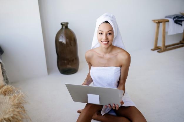 Vrolijke mooie jonge vrouw freelancer in witte handdoek zit in de badkamer en maakt gebruik van een laptop