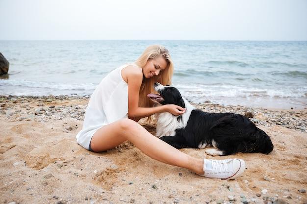 Vrolijke mooie jonge vrouw haar hond knuffelen op het strand