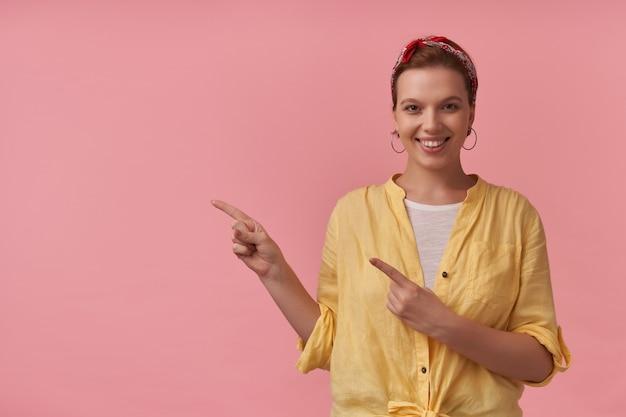 Vrolijke mooie jonge vrouw in geel overhemd met hoofdband op het hoofd die naar de zijkant op lege ruimte over roze muur wijst. camera kijken