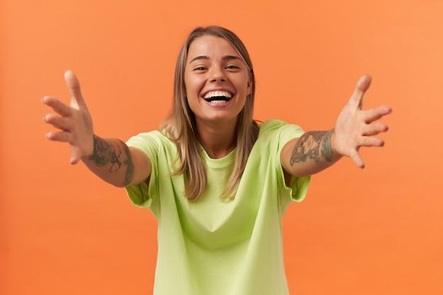 Vrolijke mooie jonge vrouw in gele t-shirt staande en handen uitrekkend naar camera geïsoleerd over oranje muur