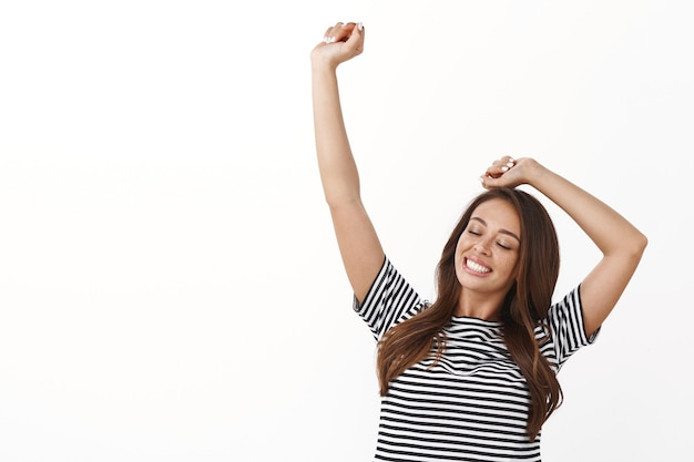 Vrolijke mooie jonge vrouw in gestreept t-shirt die handen omhoog steekt, dromerige ogen uitrekt en blij glimlacht, fantastisch voelt, witte muur