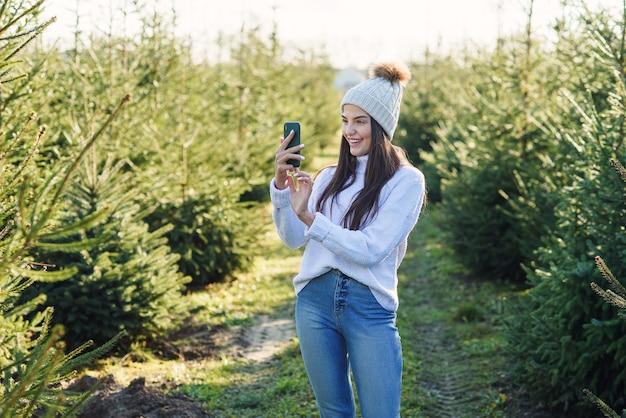 Vrolijke mooie jonge vrouw in warme hoed fotografie mooie kerstbomen tijdens het wandelen tussen bosaanplant.