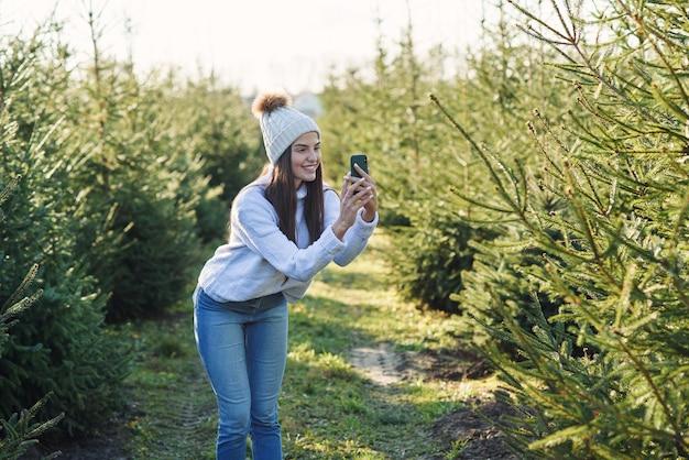Vrolijke mooie jonge vrouw in warme hoed fotografie mooie kerstbomen tijdens het wandelen tussen plantage
