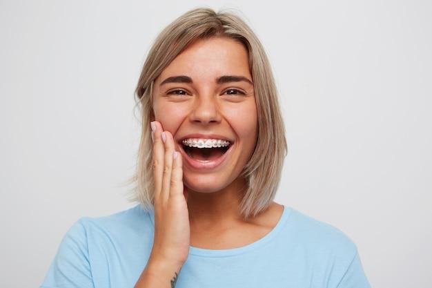 Vrolijke mooie jonge vrouw met blond haar en accolades op tanden lachen en haar gezicht aan te raken
