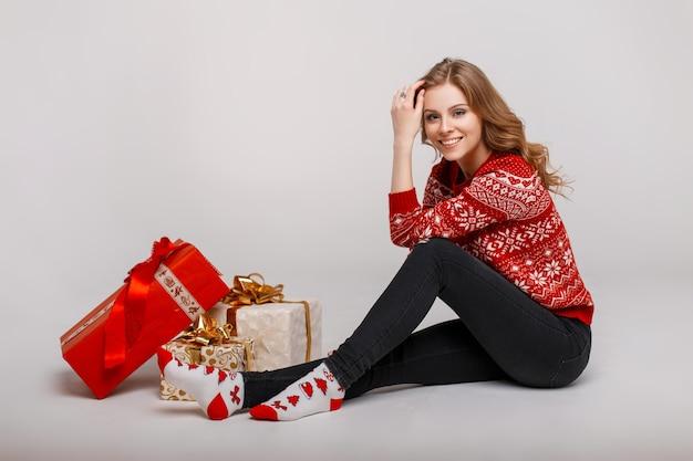Vrolijke mooie jonge vrouw met een glimlach in een rode kerst trui met sokken zitten in de buurt van een geschenk op een grijze achtergrond